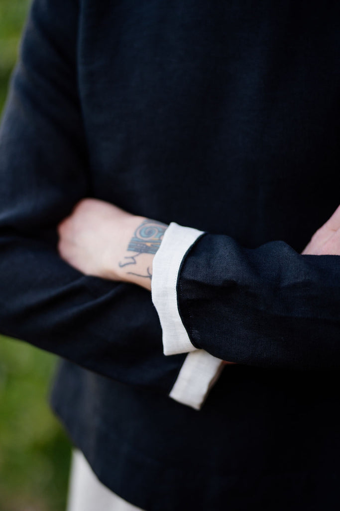 detail picture of woman linen shirt in black color with white sleeve roll ups