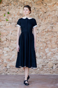 Woman in black linen dress with high waist, buttoned front and short sleeves
