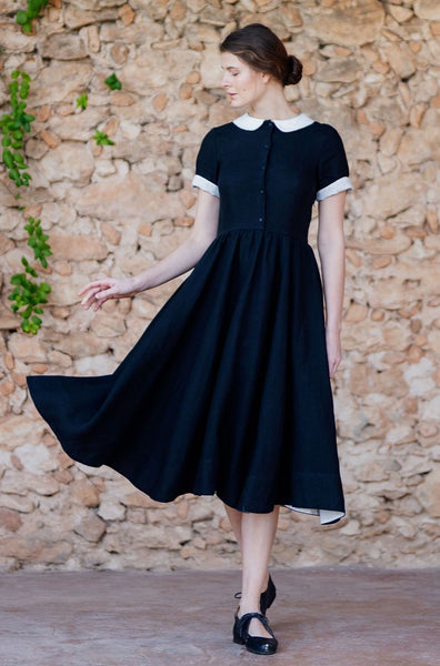 Woman wearing classic linen dress in black color with white collar and white rolled up sleeves