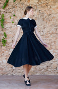 Woman turning in classic linen dress in black color with short rolled up sleeves