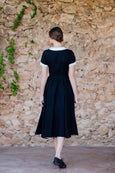 Picture from the back: woman walking in black linen dress with short sleeves and full a-line skirt