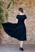 Woman walking towards wall wearing black linen dress with full a-line skirt