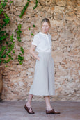 Woman in linen culotte trousers in natural sand color and pockets