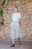 Woman walking with culotte trousers in natural linen and white short sleeved shirt