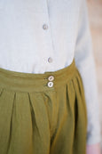 Up close detail of women trousers in linen: coconut buttons, pleats, olive green color