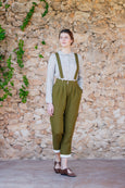 Woman wearing linen olive green trousers and the same color linen suspender belts