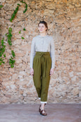 Woman in dark green linen trousers with ribbon belt