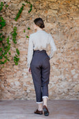 Photo from the back: woman wearing dark brown linen trousers with white hem