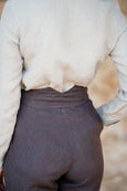 Waistline detail of women linen trousers in dark brown color