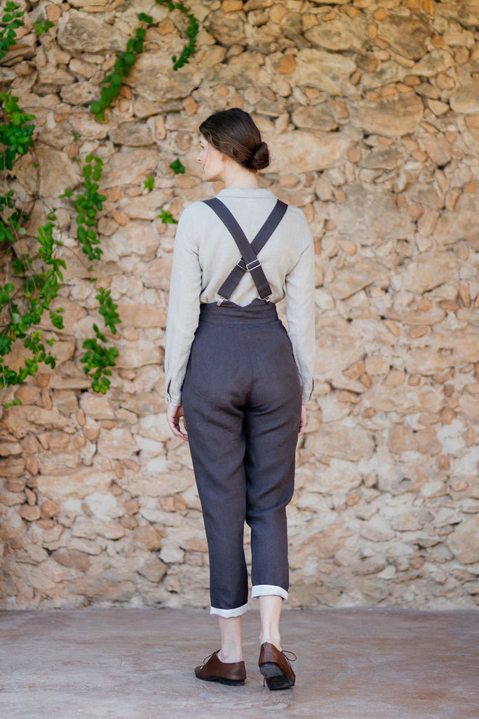 Picture from the back: woman with brown linen trousers and suspenders