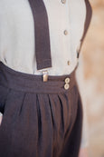 Up close detail of woman wearing peg leg trousers and dark brown suspenders