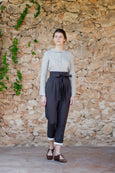 Woman walking in linen trousers with high waist and ribbon elt