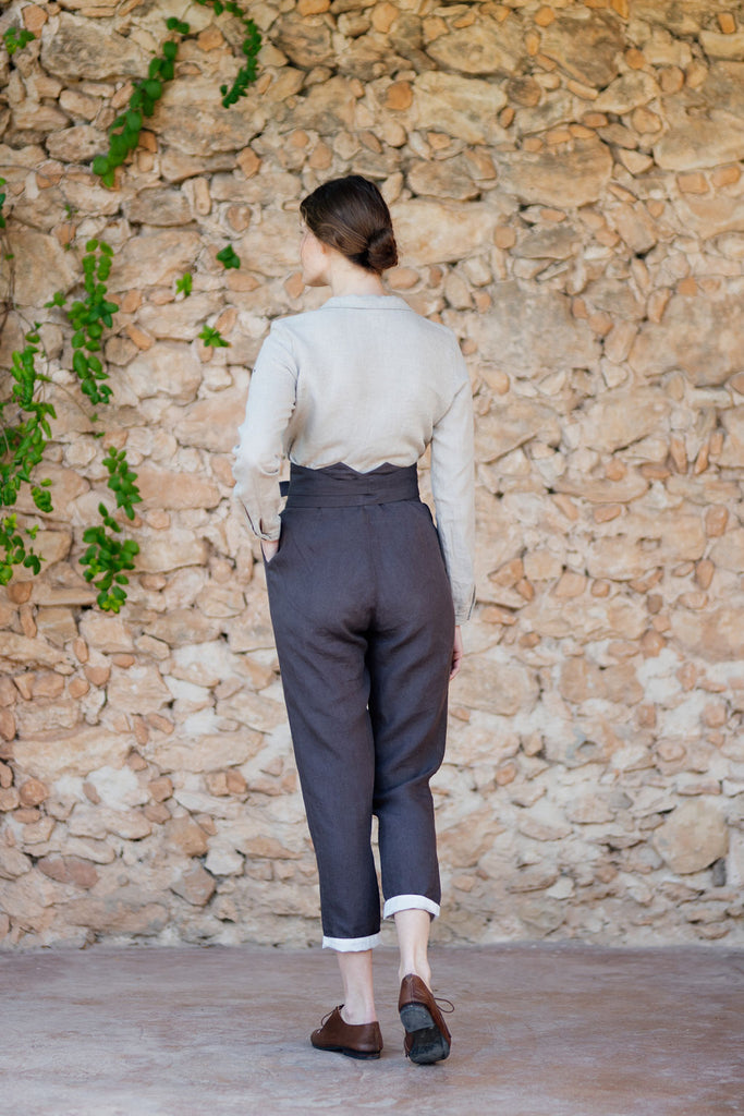 Woman wearing dark brown linen trousers with pockets