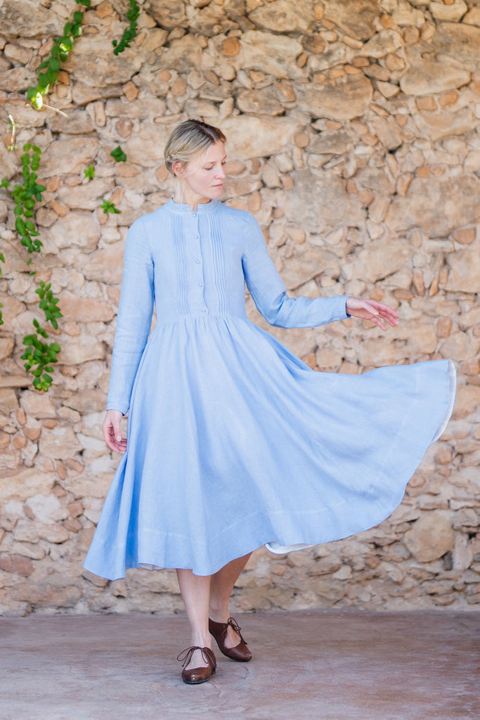 Linen dress in light blue color with pleated front detail, long sleeves and full a-line skirt