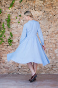 Woman turning in linen dress with full skirt in light blue color, long sleeves and pockets