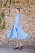 Woman in linen dress in sky blue color, with pleated front detail and long sleeves