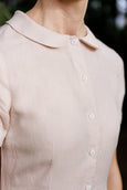 Woman in black linen loose dress with white collar walking towards a wall