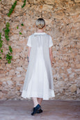 Photo from the back: woman walking in white linen dress with natural linen apron on top