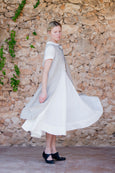 Woman in light sand apron and white linen dress