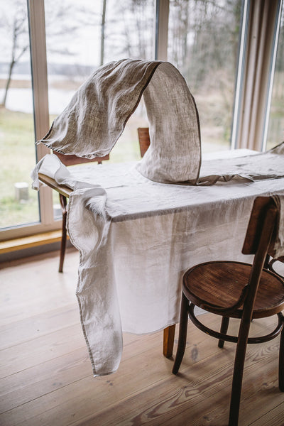 Natural linen table runner placed on a table, image from the front