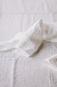 White linen towel placed on a table, up close image