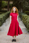 Woman wearing red classic dress with short sleeves, picture from the front.
