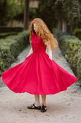 Model wearing red classic dress with short sleeves, image from the front.