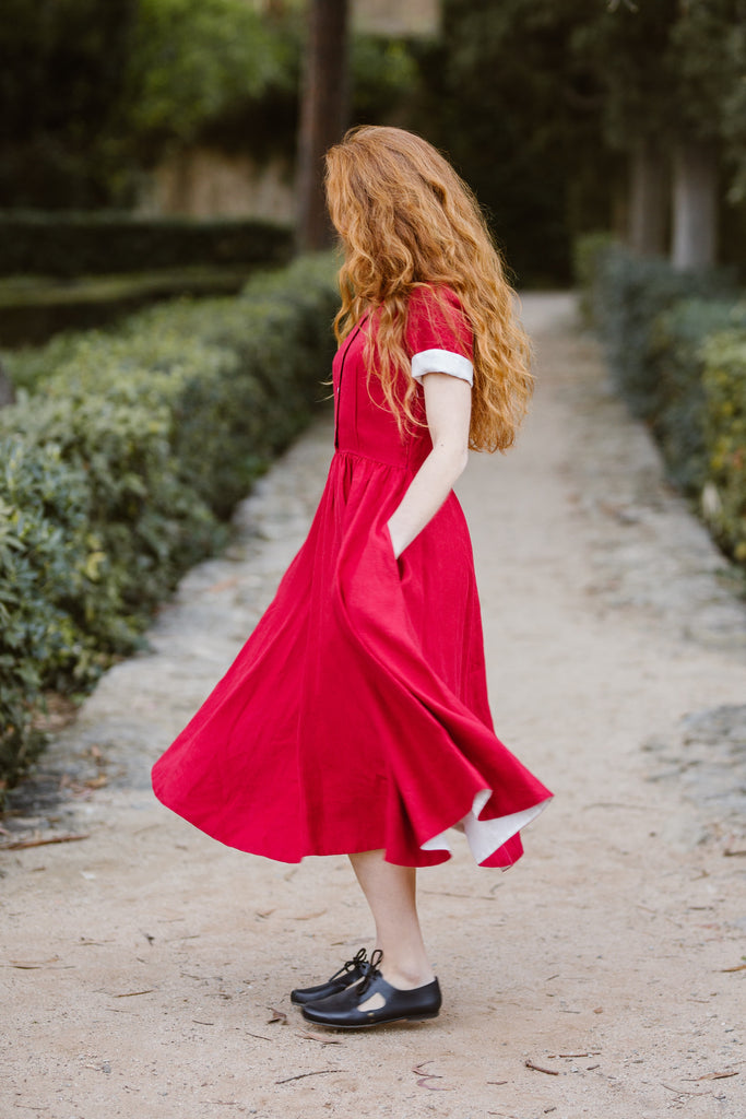 Woman wearing red classic dress with short sleeves, image from the side.