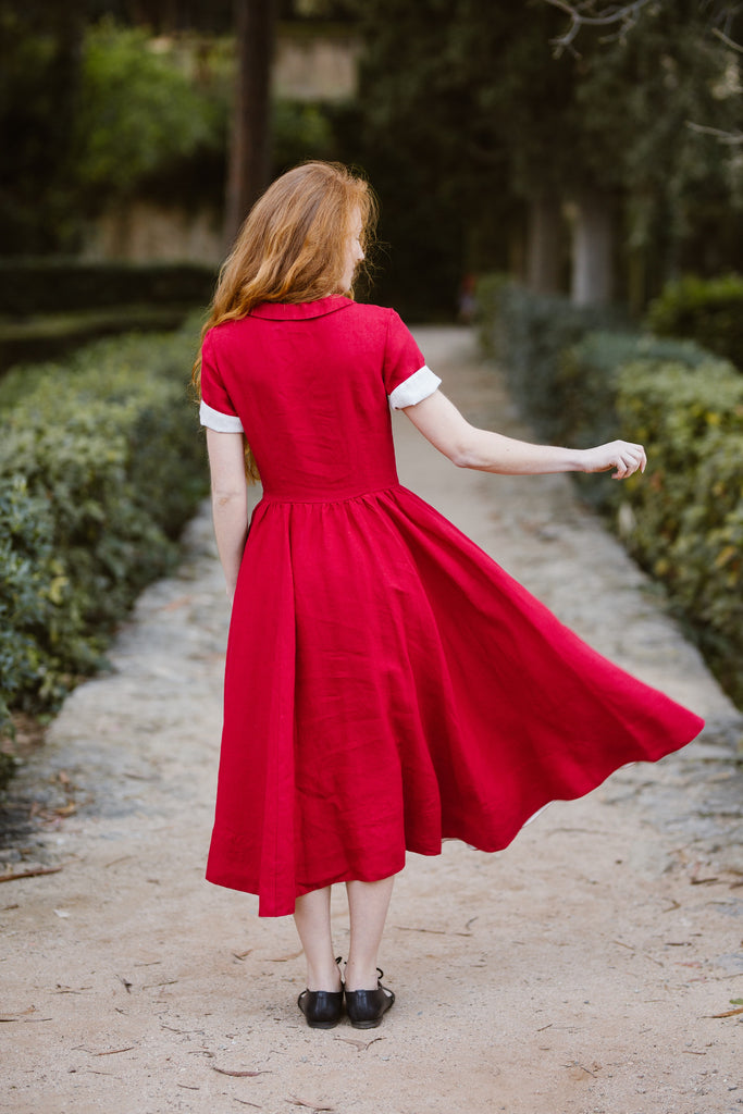 Woman wearing red classic dress with short sleeves, picture from the back.