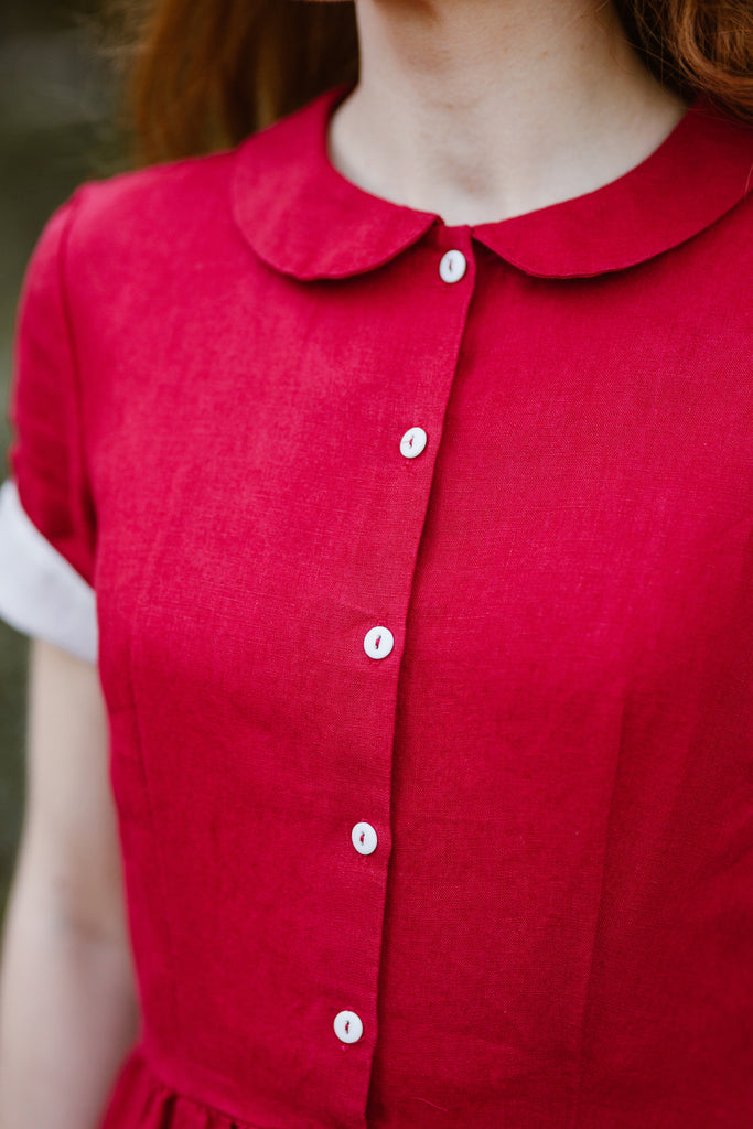 Woman wearing red classic dress with short sleeves, up close image from the front.