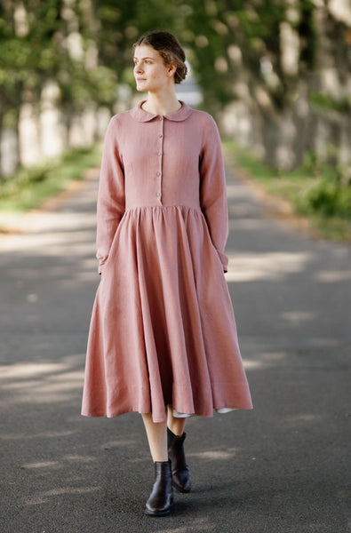 Woman wearing classic rose dress with long sleeves, picture from the front.