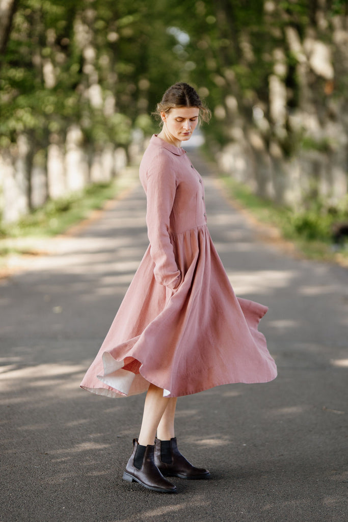 Woman wearing classic rose dress with long sleeves, picture from the side.