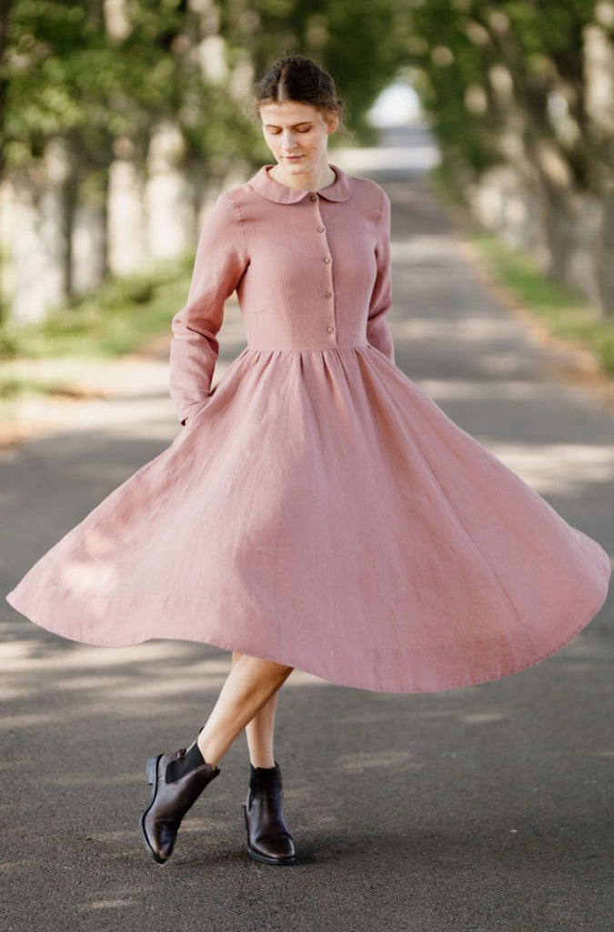 Model wearing classic rose dress with long sleeves, image from the front.