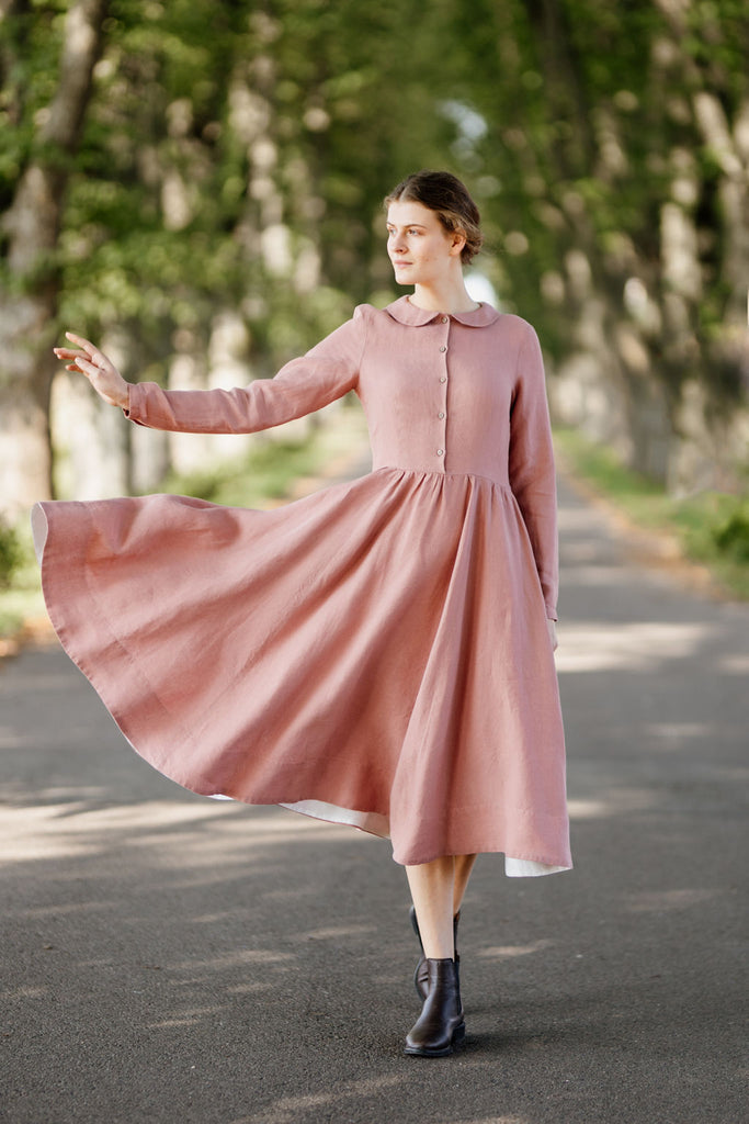 Model wearing classic rose dress with long sleeves, picture from the front.