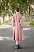 Model wearing classic rose dress with long sleeves, image from the back.
