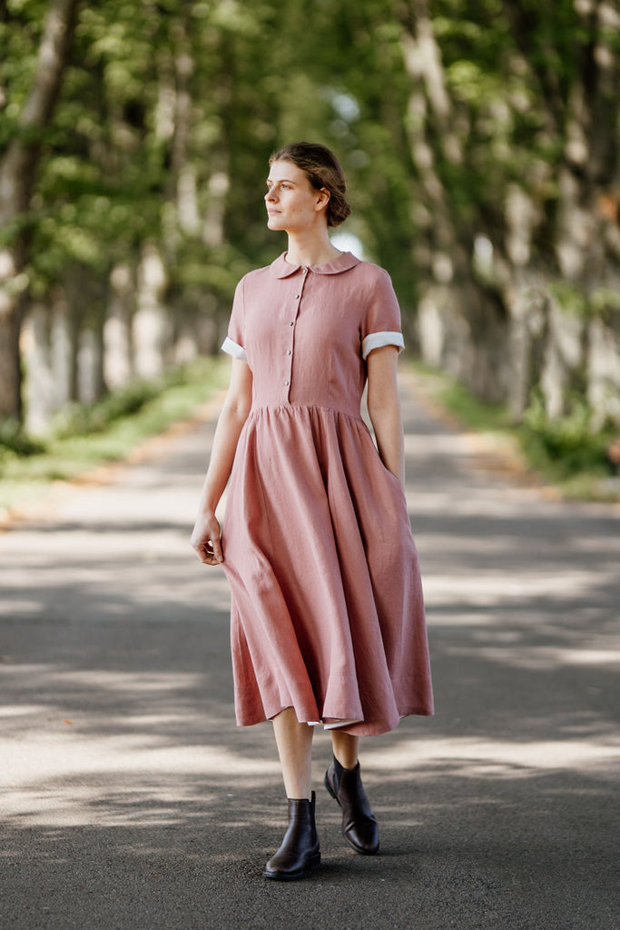Model wearing rose color classic dress with short sleeves, picture from the front.