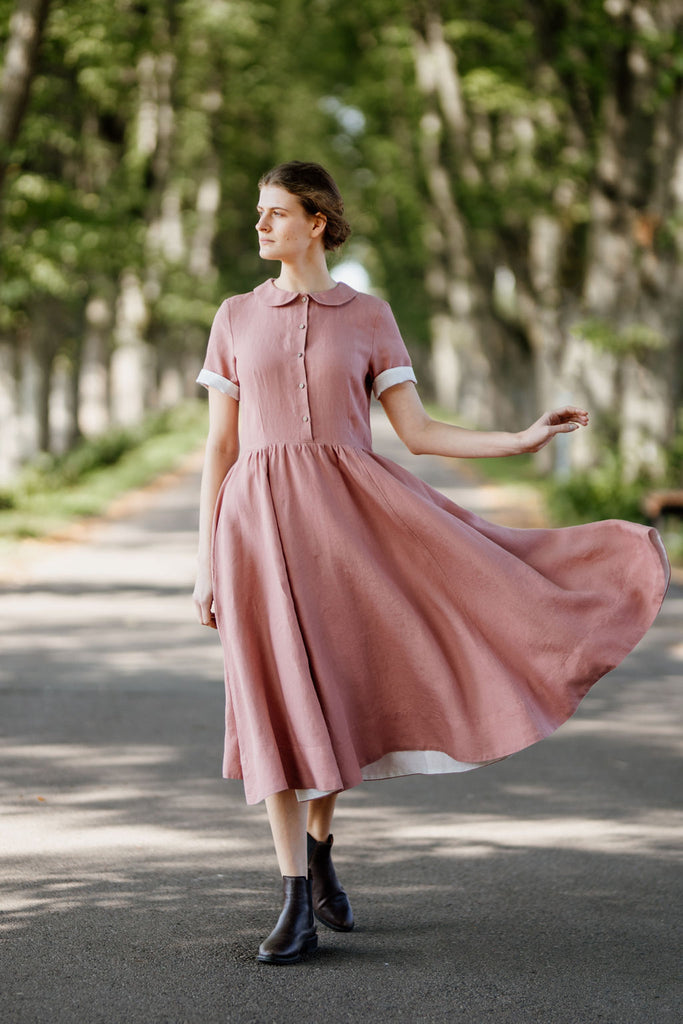 Woman wearing rose color classic dress with short sleeves, picture from the front.