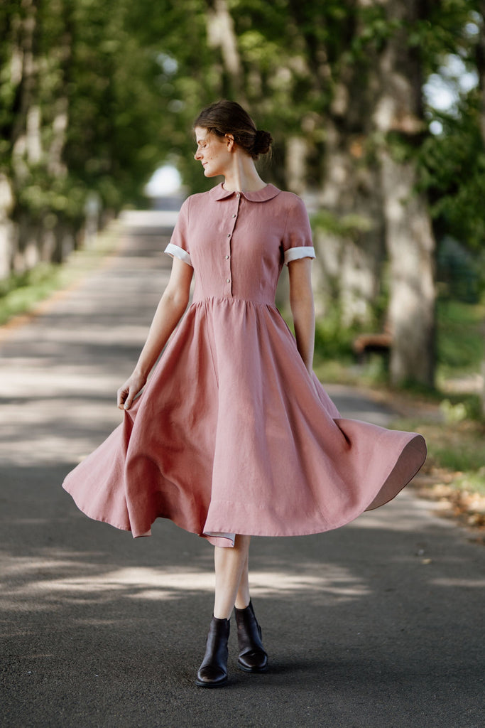 Model wearing rose color classic dress with short sleeves, image from the front.