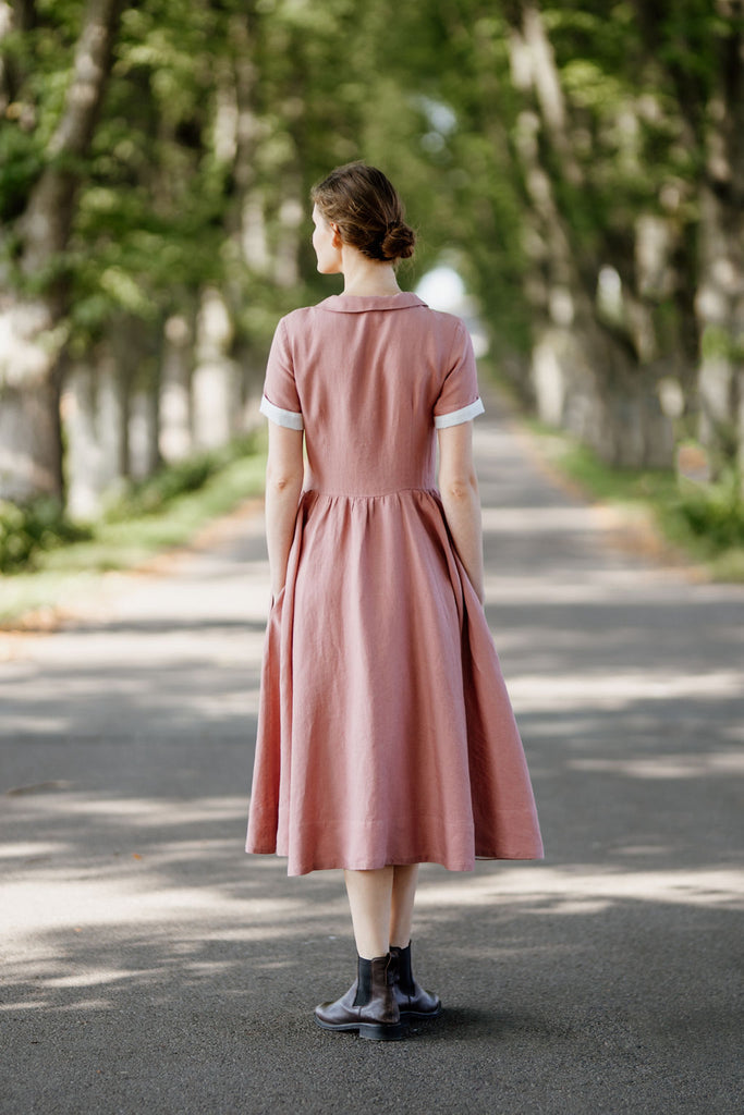 Woman wearing rose color classic dress with short sleeves, picture from the back.