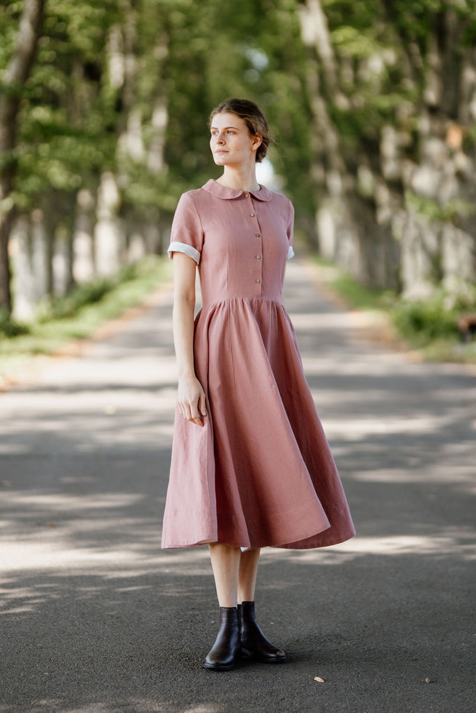 Woman wearing rose color classic dress with short sleeves, picture from the side.