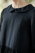 Woman wearing black dress with long sleeves, up close picture from the front.