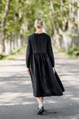 Woman wearing black dress with long sleeves, picture from the back.