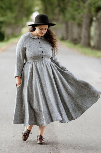Woman wearing twill linen classic dress with long sleeves, picture from the front.