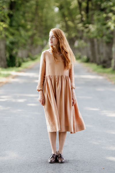 Woman wearing beige color smock dress with long sleeves, image from the front