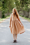 Woman wearing beige color smock dress with long sleeves, picture from the front