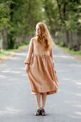Model wearing beige color smock dress with long sleeves, image from the front