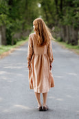 Woman wearing beige color smock dress with long sleeves, picture from the back