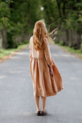 Woman wearing beige color smock dress with long sleeves, image from the back