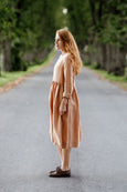 Woman wearing beige color smock dress with long sleeves, picture from the side