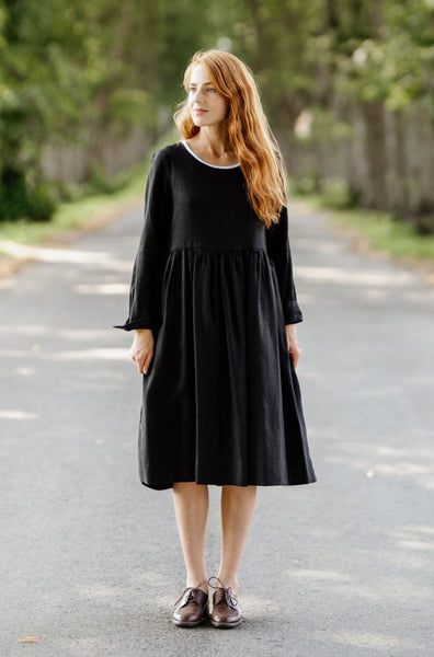 Woman wearing black smock dress with long sleeves, picture from the front